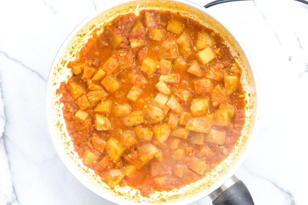 aloo matar simmering in a white skillet