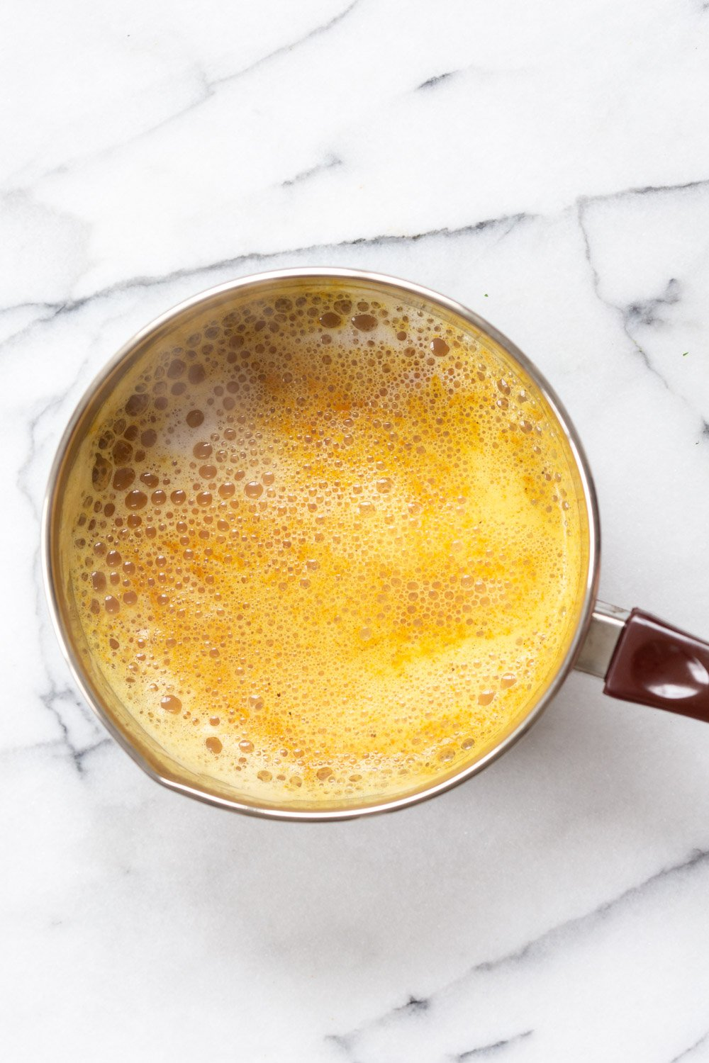 Turmeric Chai latte in a saucepan made with our Golden Chai Mix