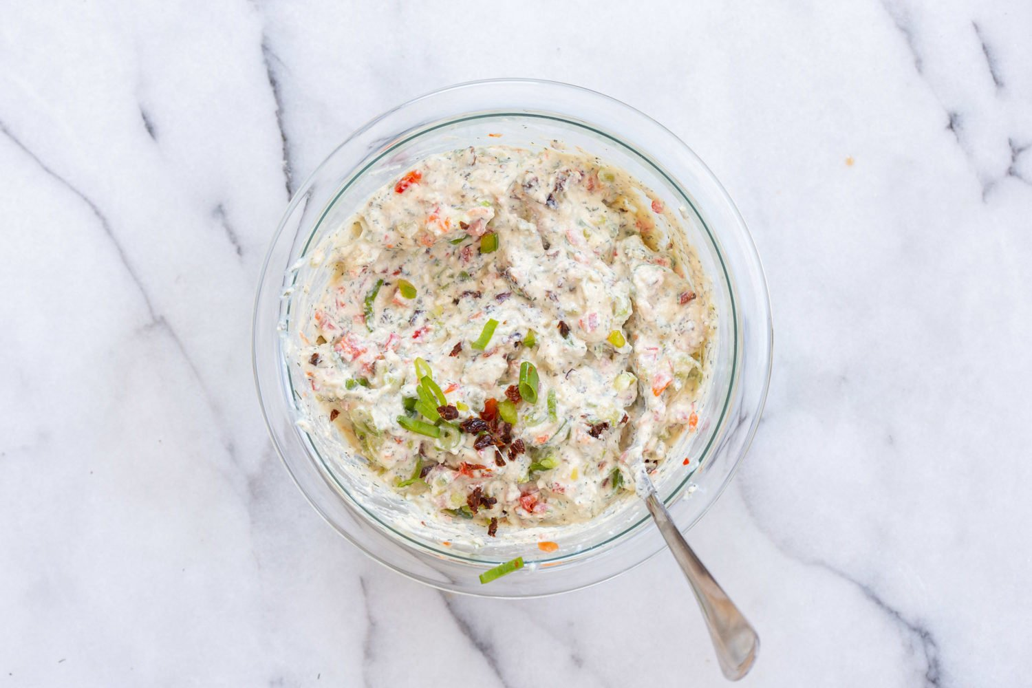 Dairy free cream cheese mixed with veggies in a bowl for our Vegan Tortilla Roll ups recipe