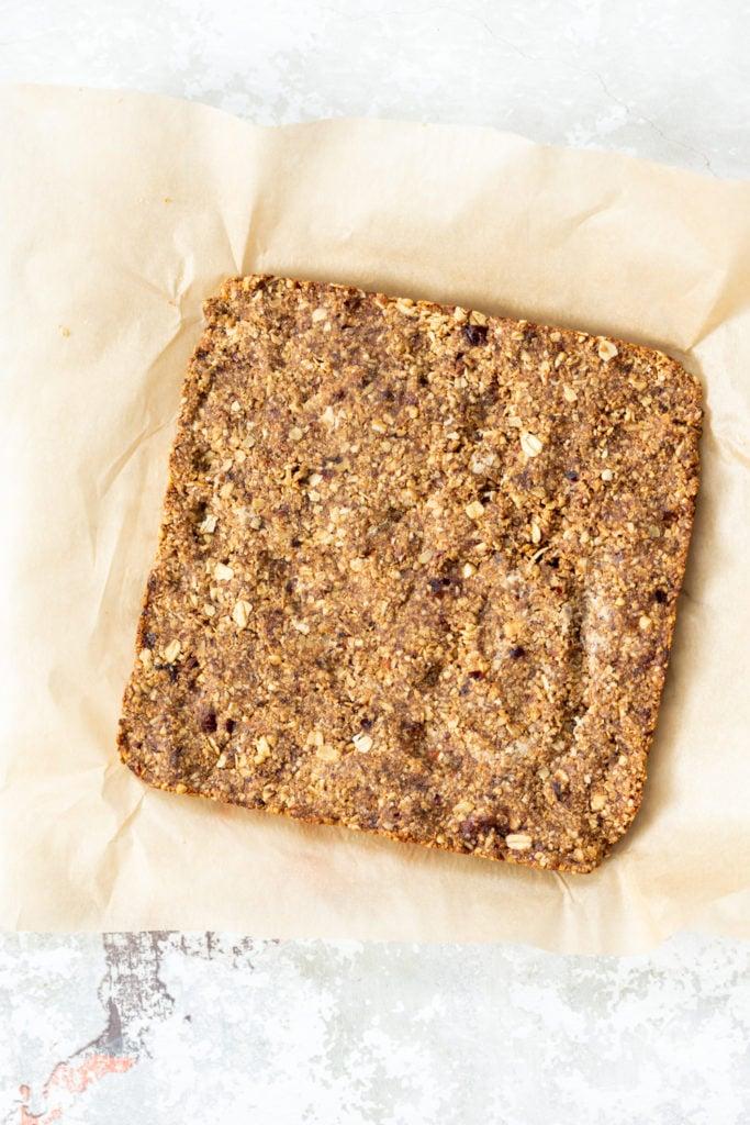 overhead shot of vegan banana granola bars on a sheet of baking paper ready to be cut