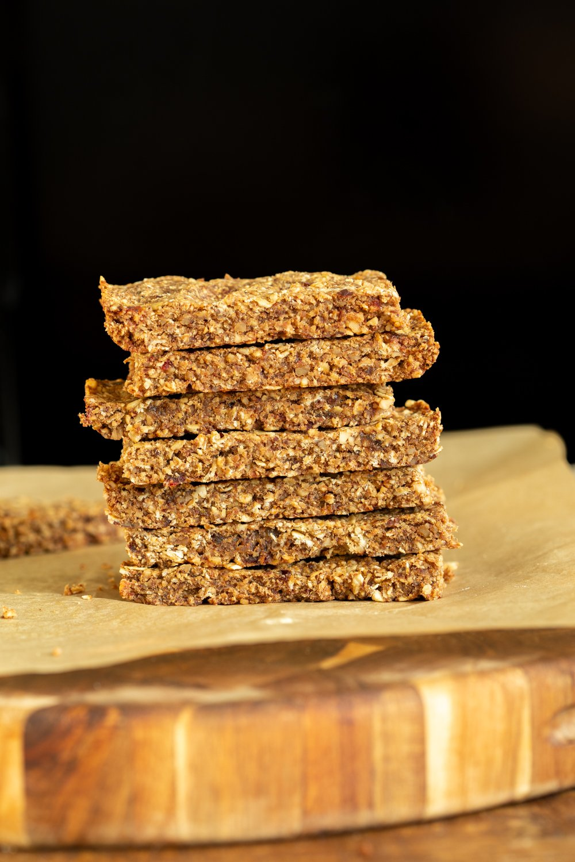a stack of vegan caramelized banana & nut granola bars against a black background