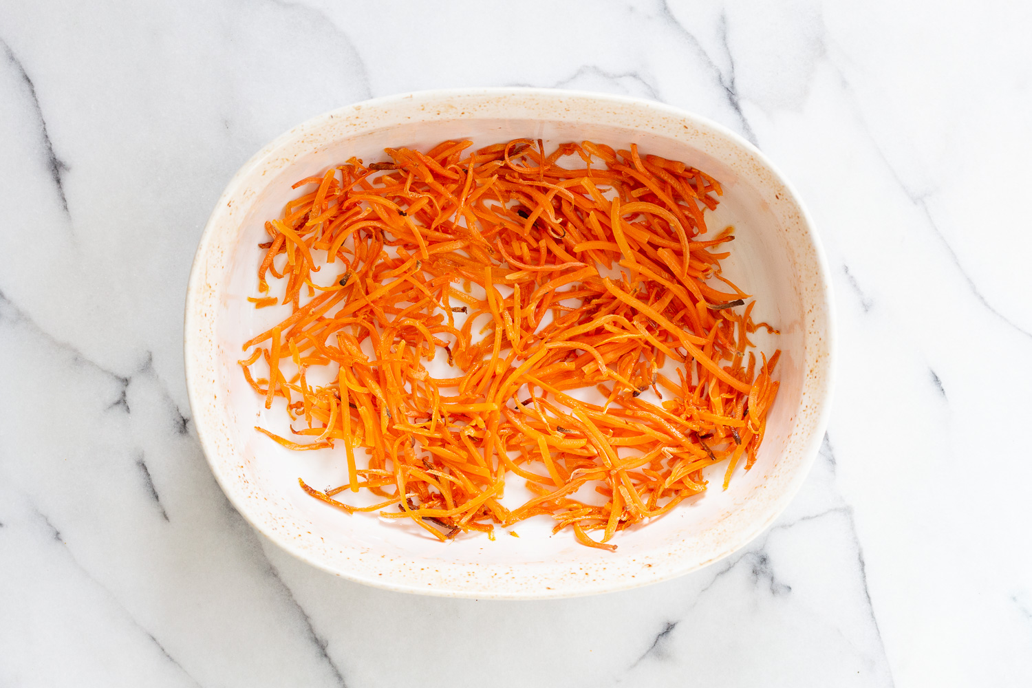 Roasted Carrots for our Vegan Carrot Cake Baked Oatmeal in a white baking dish