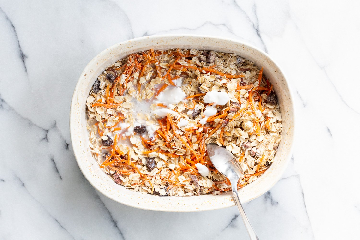 Non Dairy milk mixed with dry ingredients for Our Vegan Carrot Cake Baked Oatmeal in a baking dish