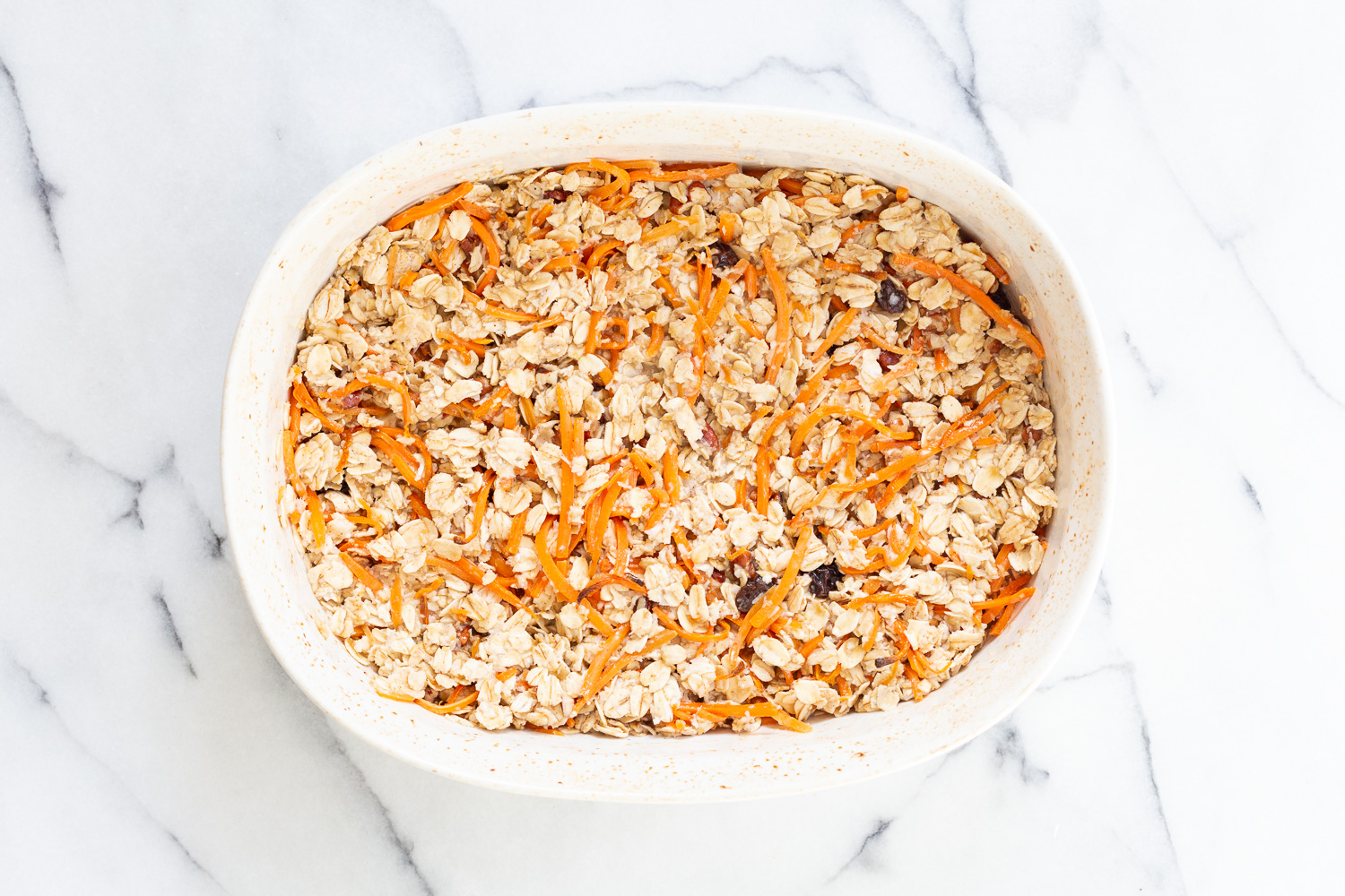 Our Vegan Carrot Cake Baked Oatmeal ready tobake in a white baking dish