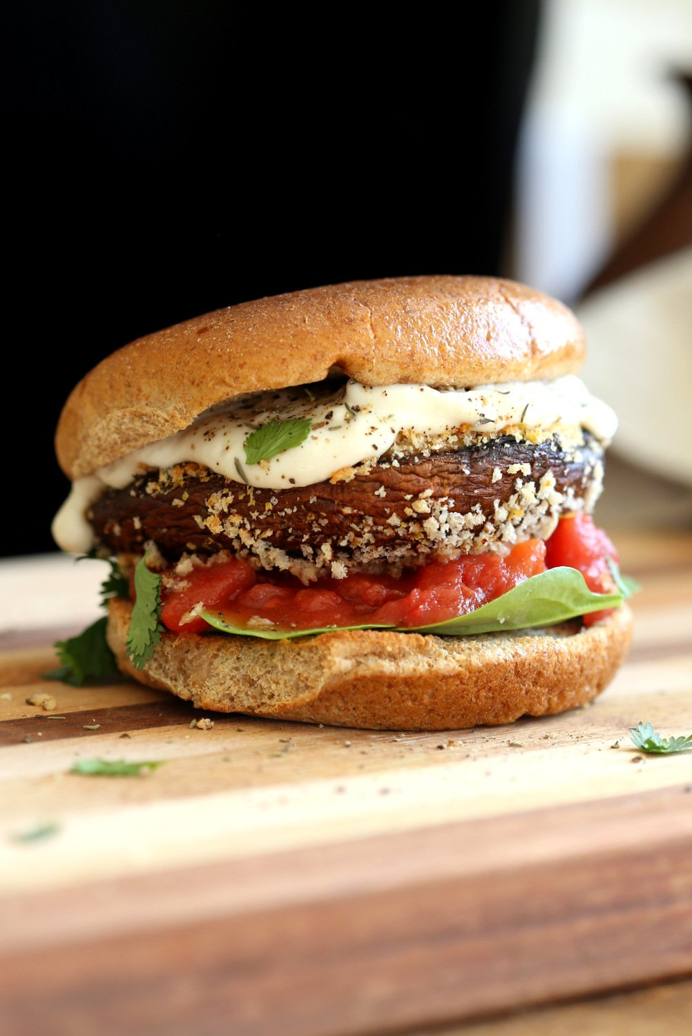 Our Vegan Portobello Mushroom Burger on a wood board against black background
