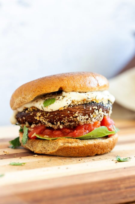 Vegan Portobello Mushroom Burger. Portobello marinated and stuffed with vegan mozzarella, then breaded to make Crispy Portobello Sandwiches! Top with more vegan mozzarella cream, fresh herbs. #Vegan #Recipe #VeganRicha #VeganPortobelloMushroomBurger #breadedportobello. Nutfree Gluten-free options