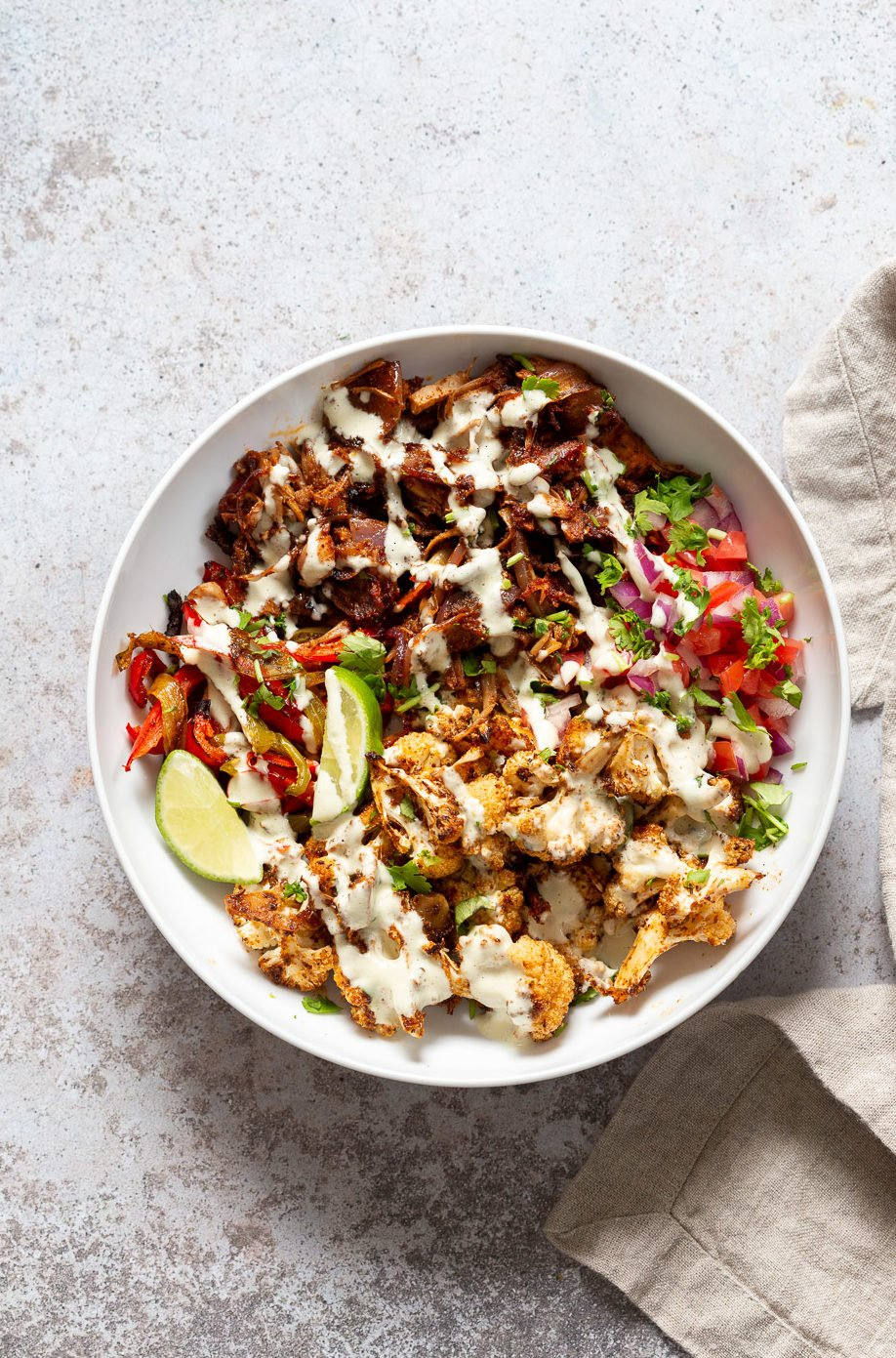 Chili Lime Roasted Veggies & Jackfruit drizzled with jalapeno cream sauce in a White Bowl