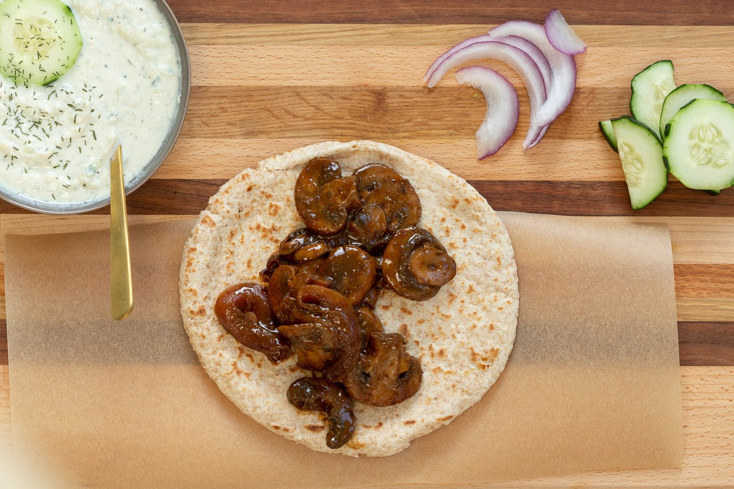 Assembly of Vegan Gyros with Mushrooms and tzatziki on Wood Board