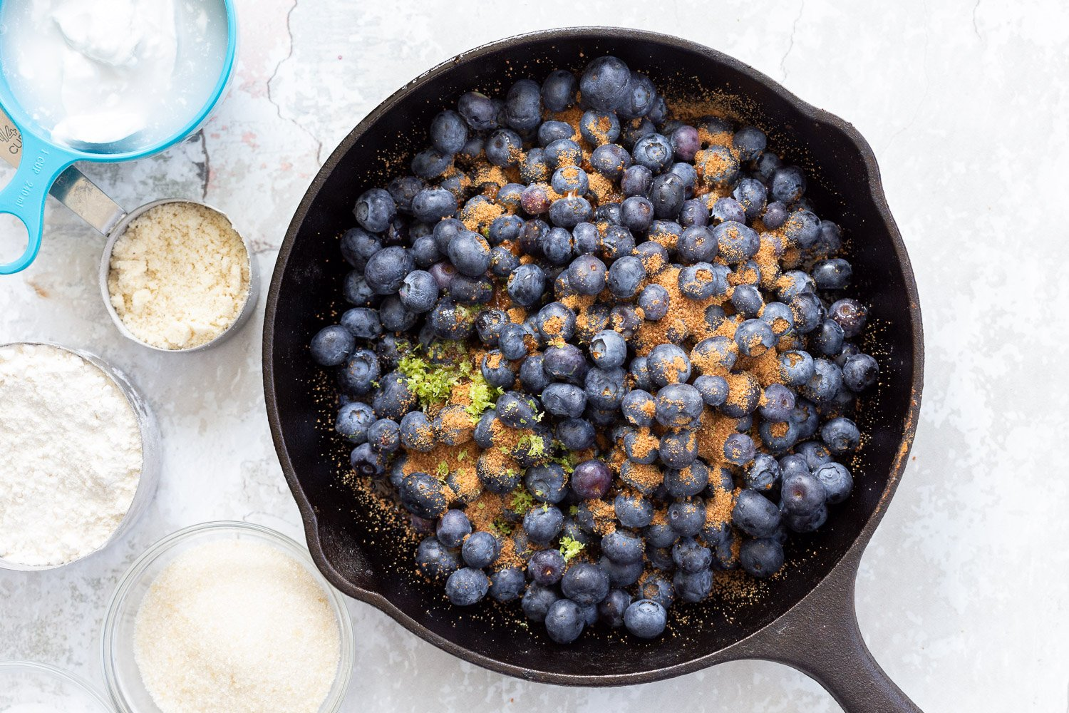 Blueberries sugar and lemon zest in cast iron skillet for our Vegan Blueberry Cobbler