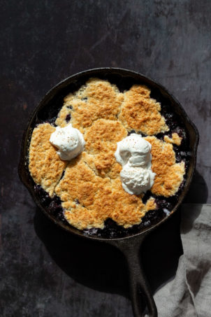 Our Vegan Blueberry Cobbler in a Cast Iron skillet over metal board