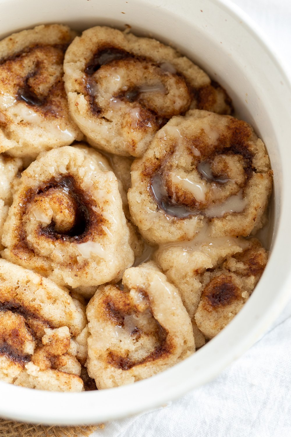 Our Vegan Gluten free Cinnamon rolls in a stoneware dish on marble