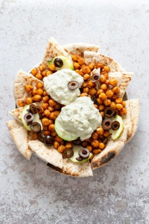 Vegan Mediterranean Nachos with Shawarma Chickpeas, Tzatziki, Olives, Cucumber, warm toasted Pita bread. Great Appetizer for parties or potluck. #Vegan #Veganricha #Mediterraneannachos