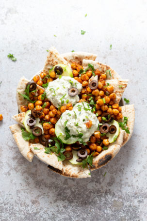 Mediterranean Nachos with Shawarma Chickpeas, Tzatziki, Olives, Cucumber, warm toasted Pita bread. Great Appetizer for parties or potluck. #Vegan #Veganricha #Mediterraneannachos