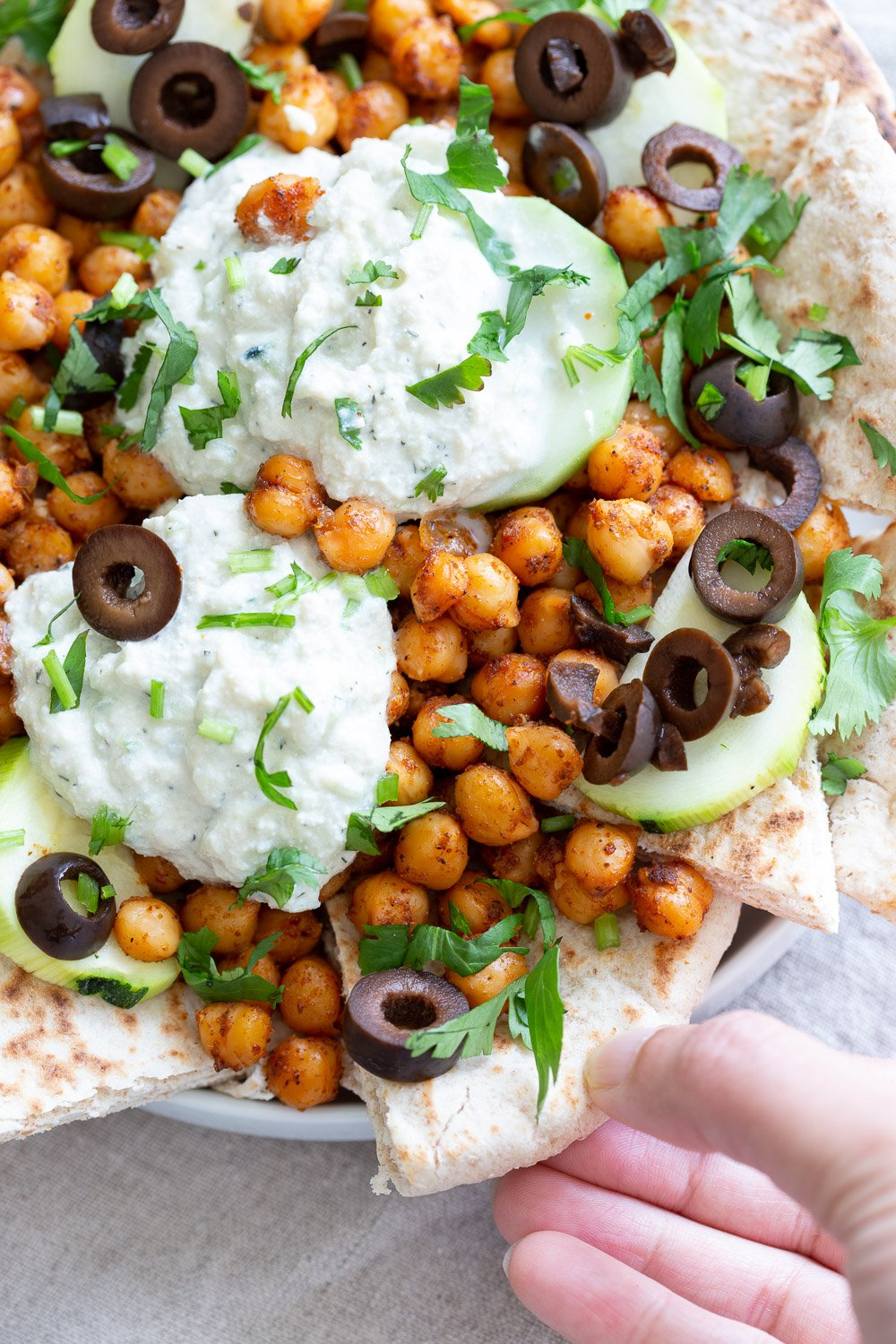 Vegan Mediterranean Nachos with Shawarma Chickpeas, Tzatziki, Olives, Cucumber, warm toasted Pita bread. Great Appetizer for parties or potluck. #Vegan #nutfree #recipe #Veganricha #Mediterraneannachos