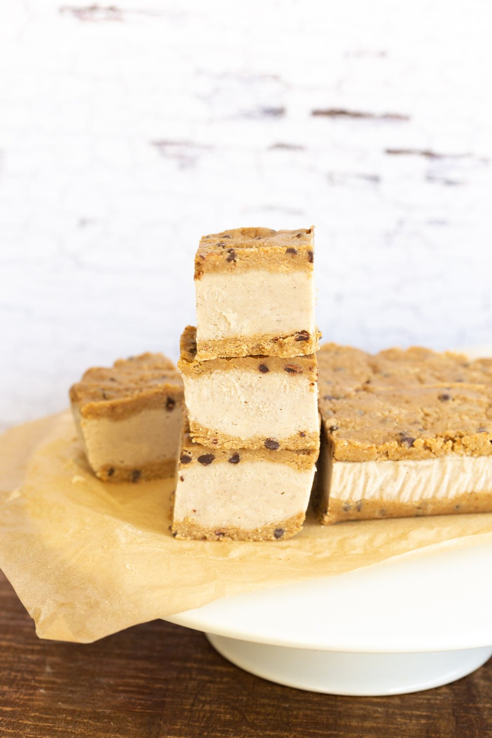 Vegan Cookie Dough Ice Cream Sandwiches stacked on a white cake stand