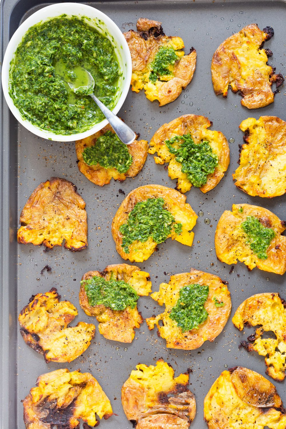 Vegan Smashed Potatoes with Chimichurri Sauce on a Grey Baking sheet