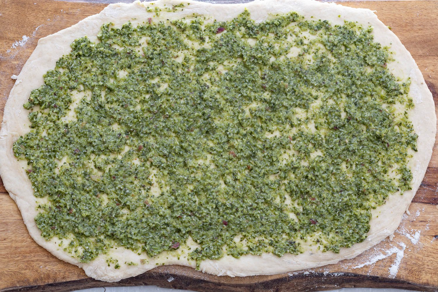 vegan pesto being spread onto rolled out pizza rolls dough