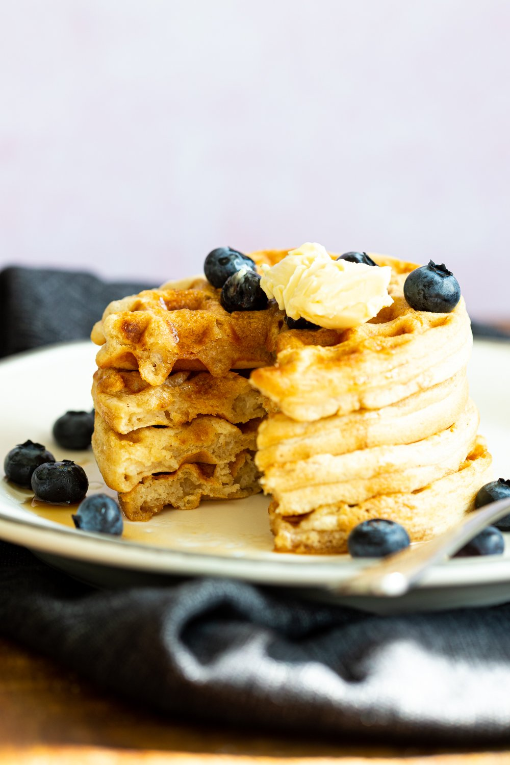 Our Easy Vegan Waffles stacked on a white plate over black napkin