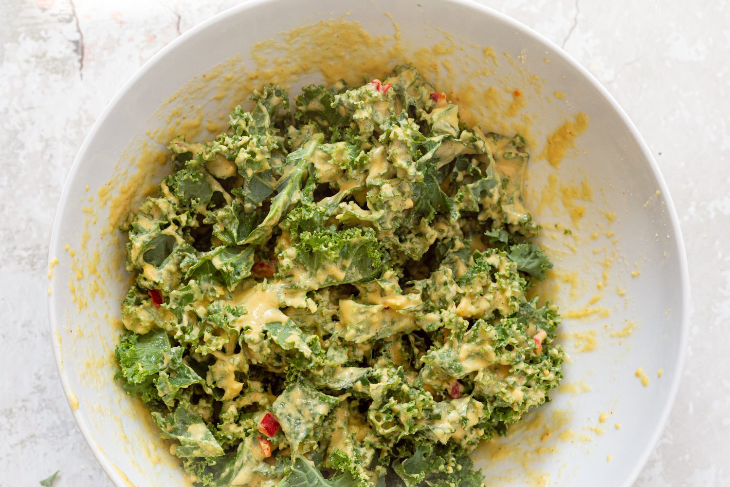 Kale leaves coated in batter, in a white bowl