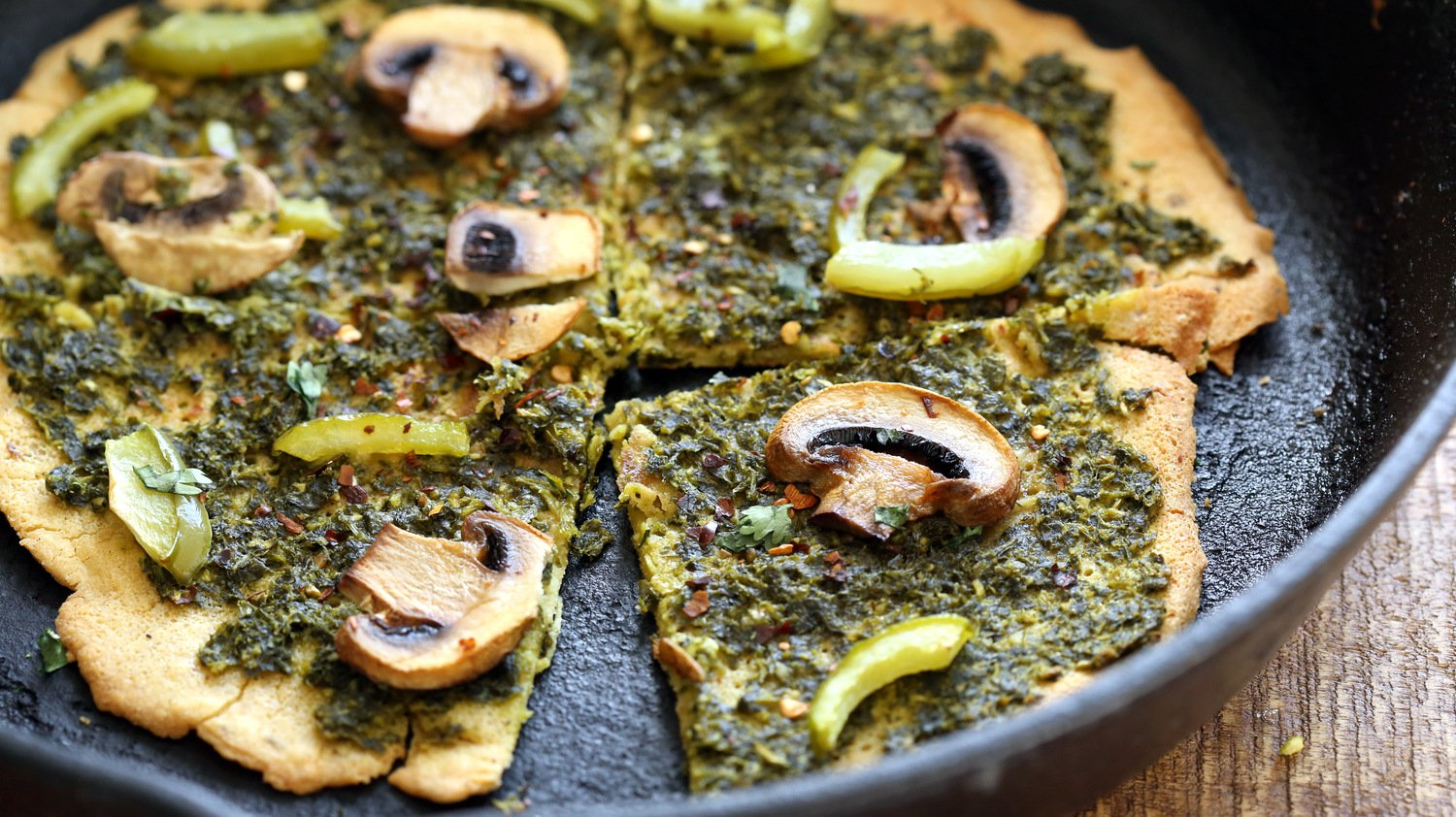 Socca Pizza with pesto and mushrooms on cast iron skillet