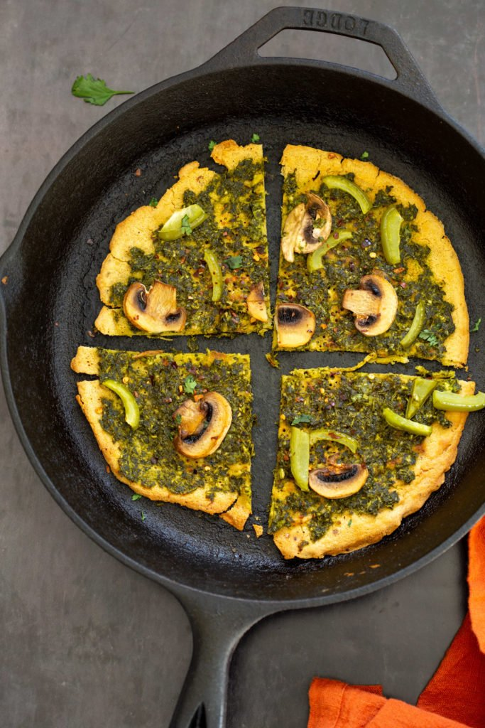 Socca Pizza with chimichurri and mushrooms on cast iron skillet