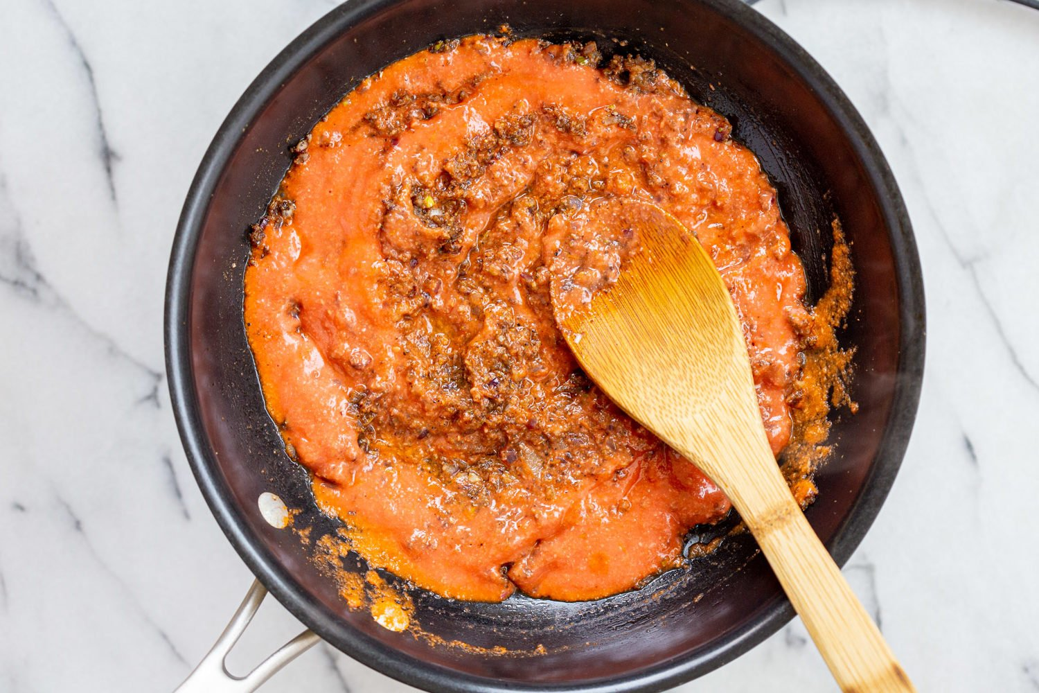 Tomato puree for our Vegan Keema Madras on a black skillet