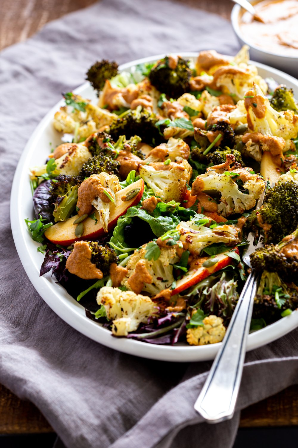 Roasted Broccoli Cauliflower Salad with Sun dried Tomato Dressing on white serving platter