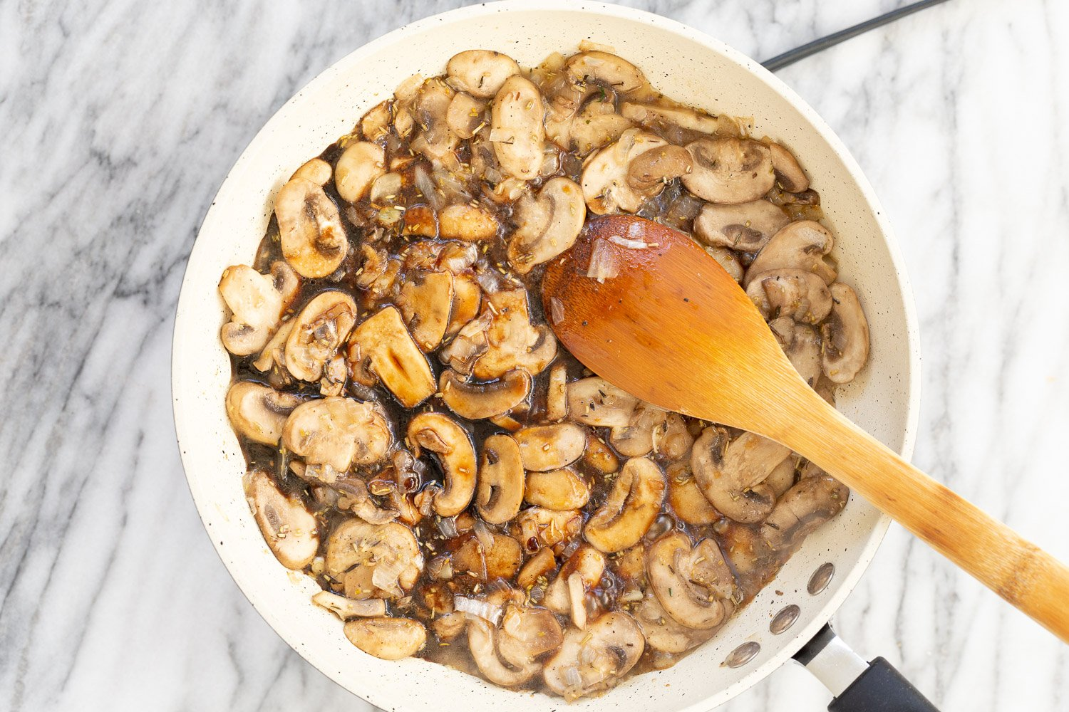 Mushrooms with sauces and herbs in a white skillet
