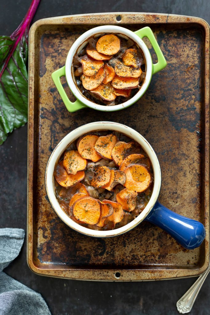 Our Vegan Mushroom Pot Pie in green and blue baking dishes on a baking sheet