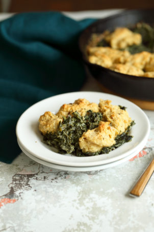 Vegan Creamed spinach in white plate and iron skillet