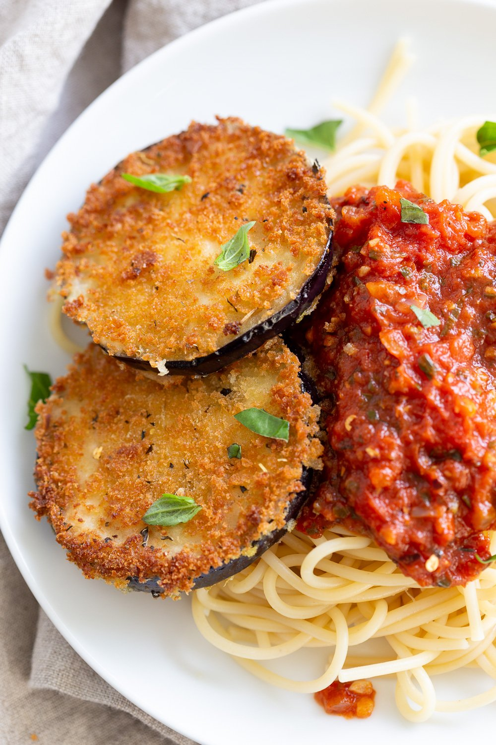 Vegan Eggplant Parmesan with spaghetti in white plate