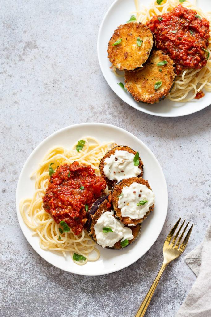 Vegan Eggplant Parmesan with spaghetti on white plates