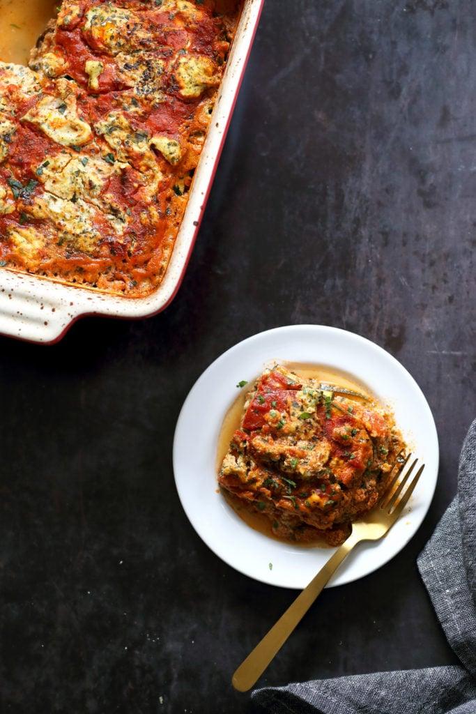 Our Vegan Gluten free Zucchini Lasagna in a cream baking dish and white plate