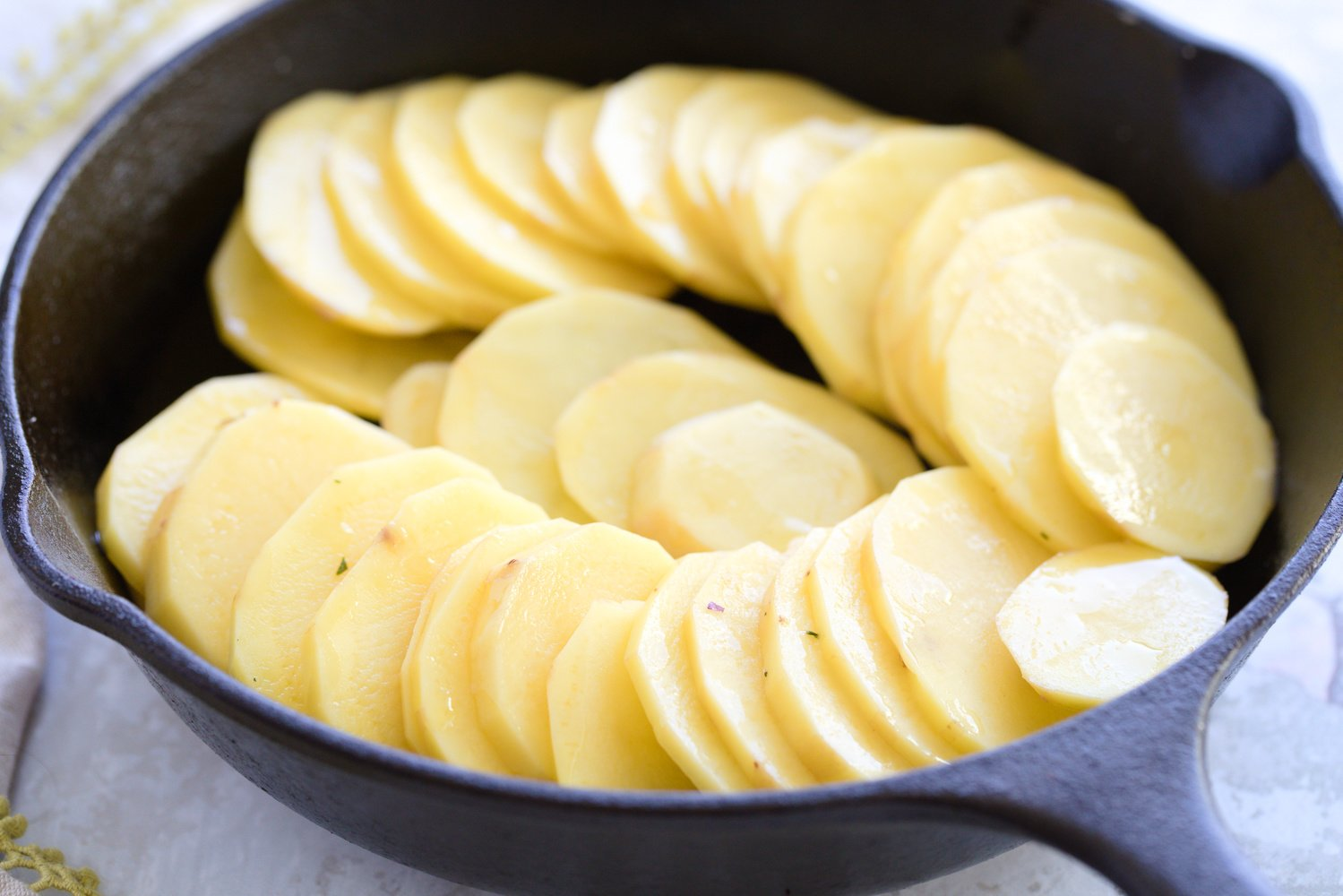 sliced potatoes in a cast iron skillet