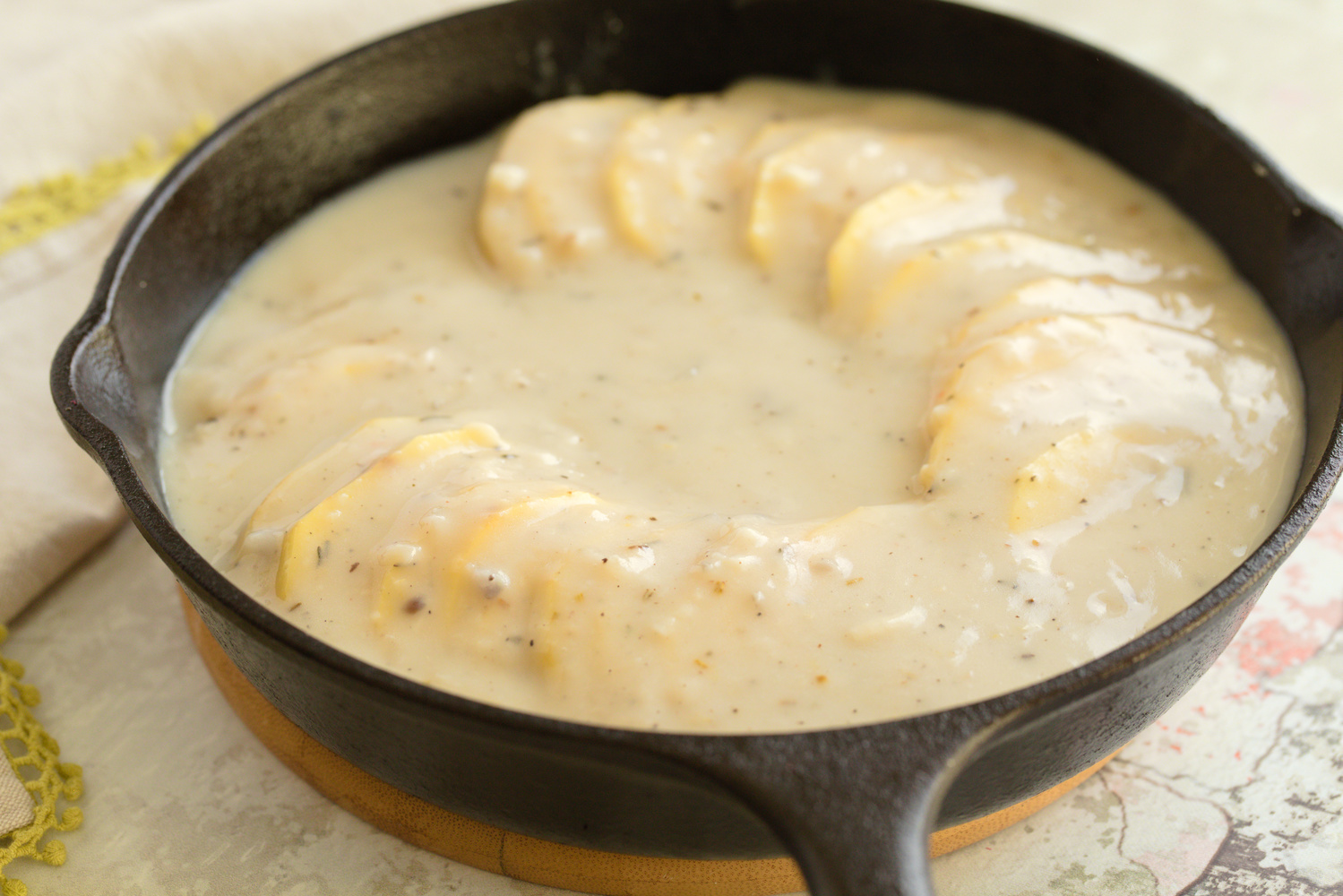 sliced potatoes drizzled with creamy cheesy sauce in a cast iron skillet