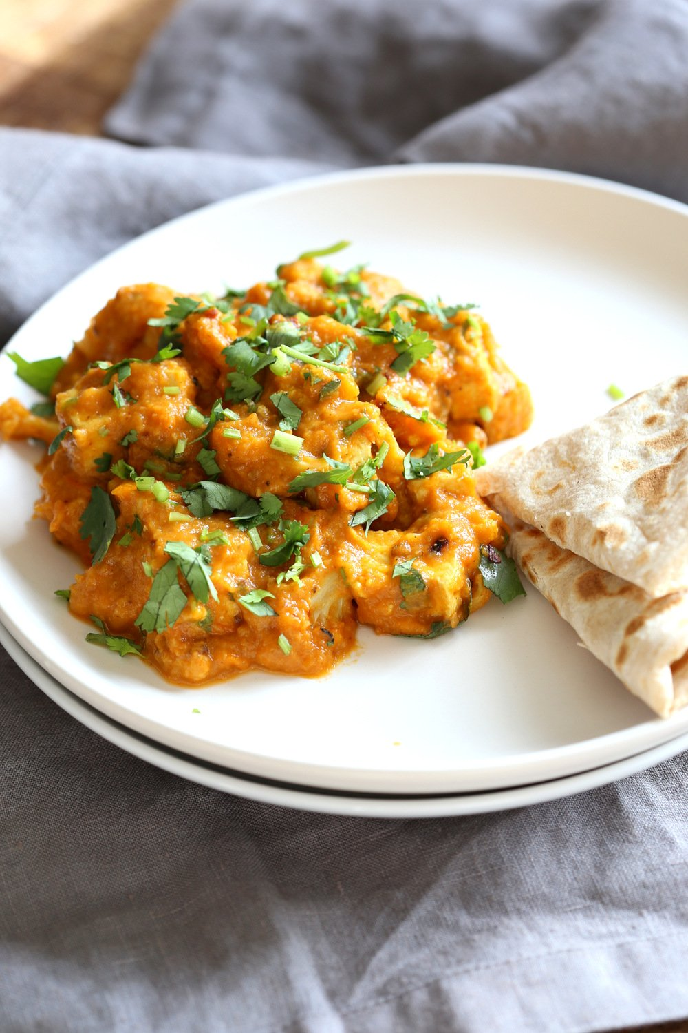Tofu and Cauliflower in Kolhapuri Sauce in a white plate with flabread