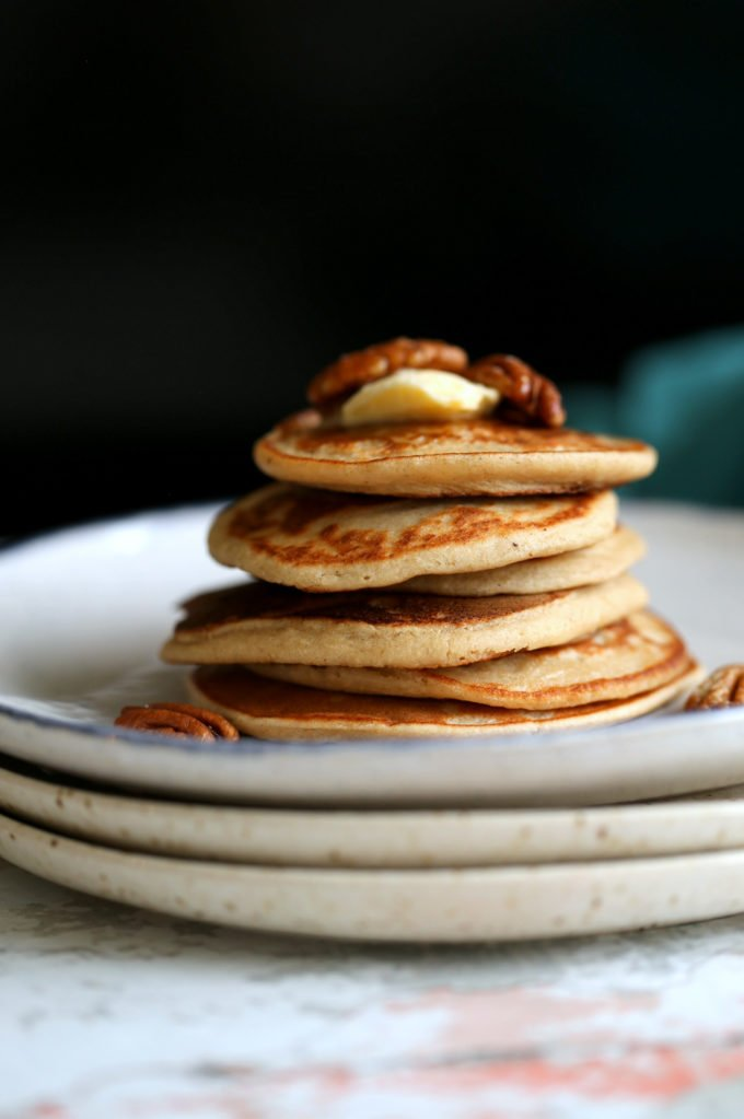 Banana Oat Pancakes Stacked on white plates