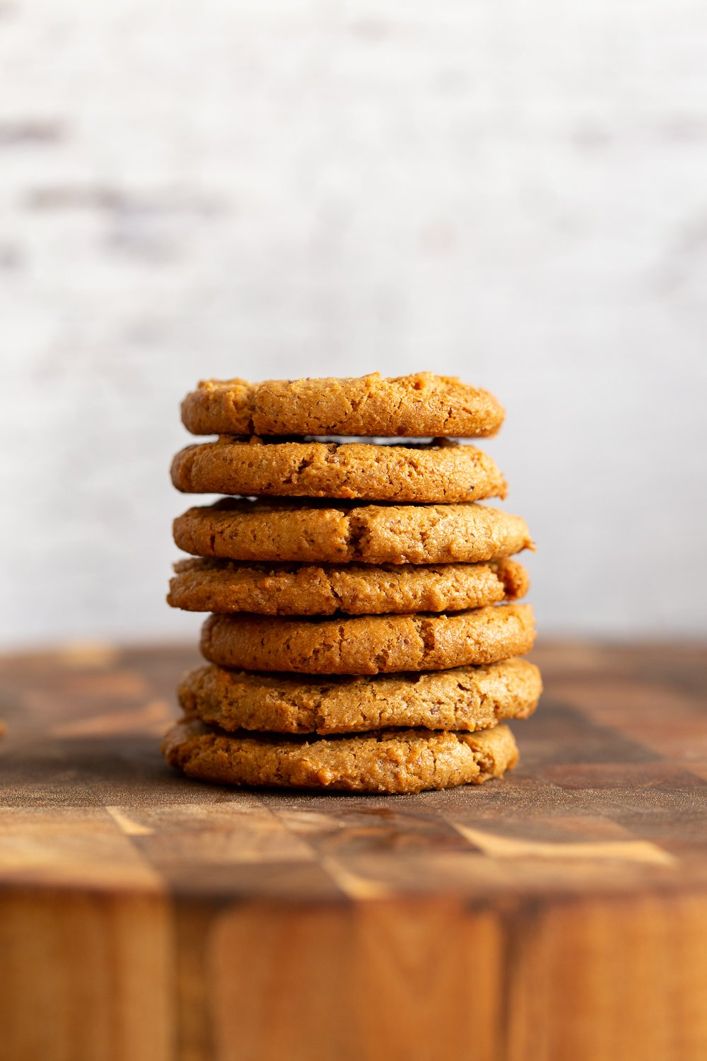 Our Chai Spice Tahini Cookies Nut free stacked on a wood board