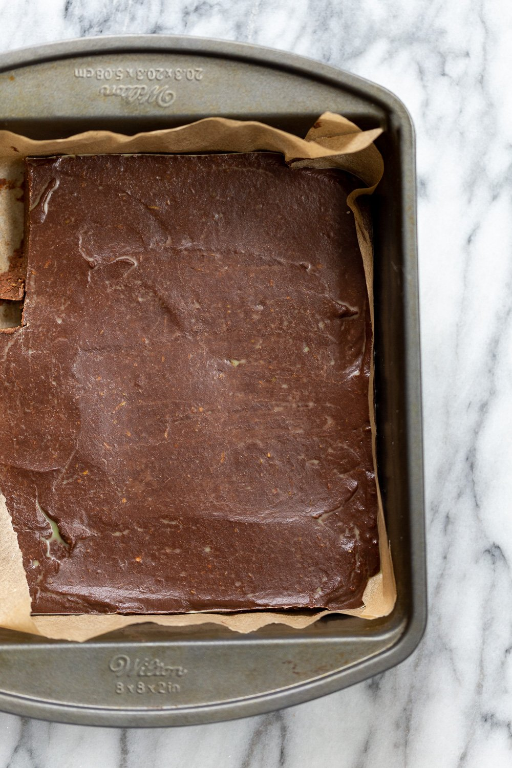Vegan Chocolate Avocado Freezer Fudge in parchment lined brownie pan