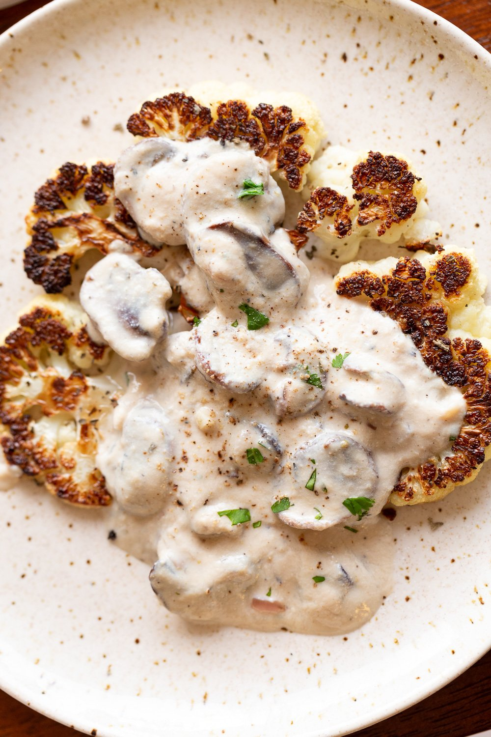 Vegan Mushroom Sauce with Cauliflower Steak on a white plat