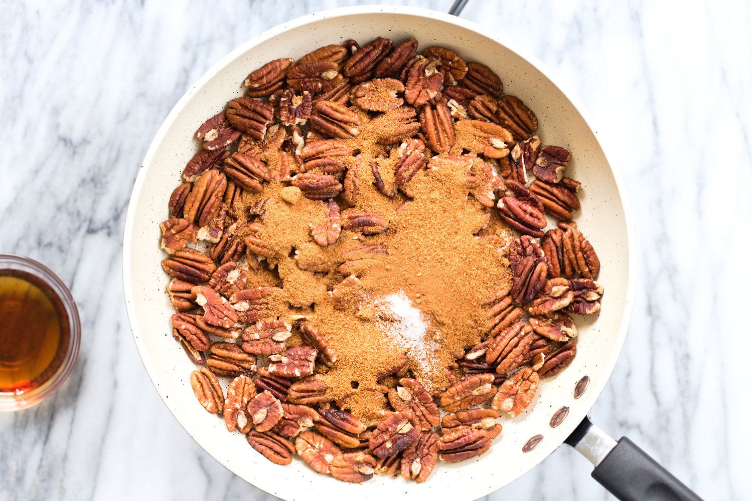 Toasted Pecans, coconut sugar, salt, spice in a white skillet