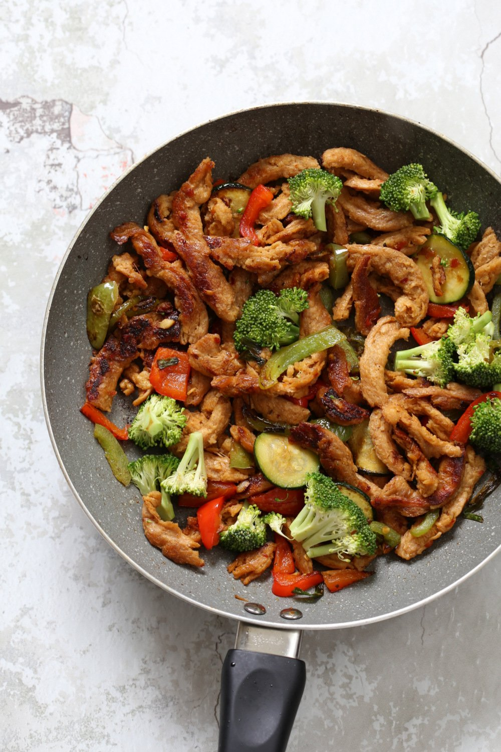 Vegegies and soy curls with general tsos sauce in grey skillet