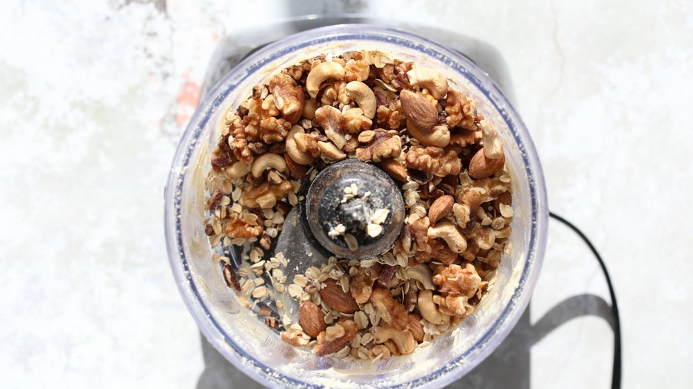 nuts and oats being added to a food processor