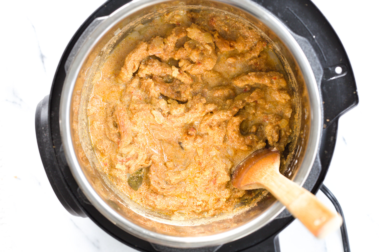vegan creamy fenugreek curry with soy curls being stirred in an instant pot