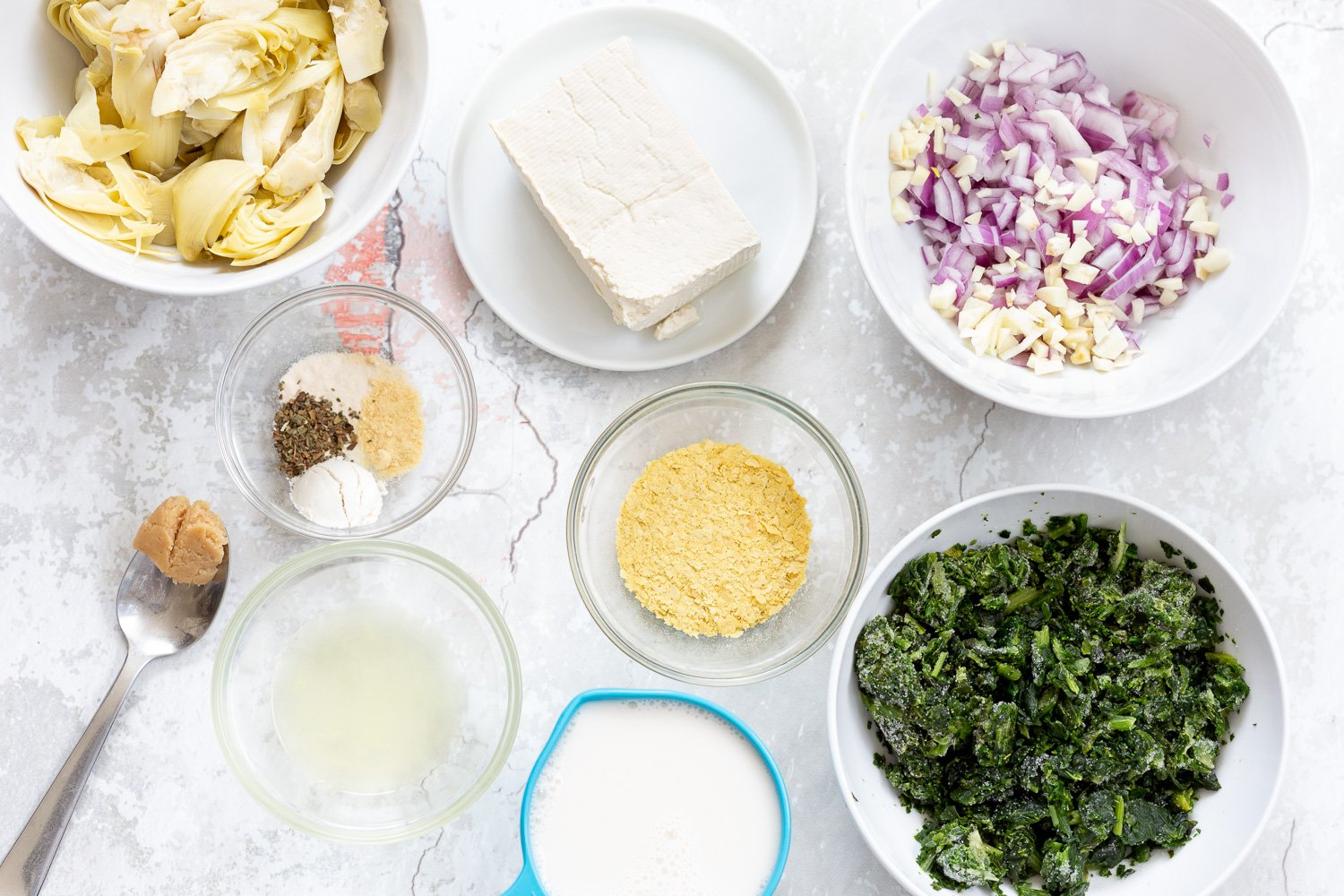 overhead shot of ingredients needed for making spinach artichoke pasta bake