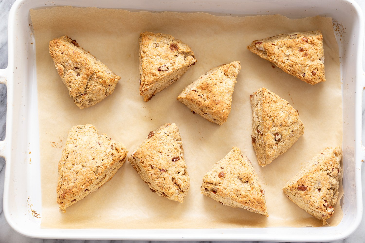 freshly baked golden brown vegan banana scones on a cookie sheet