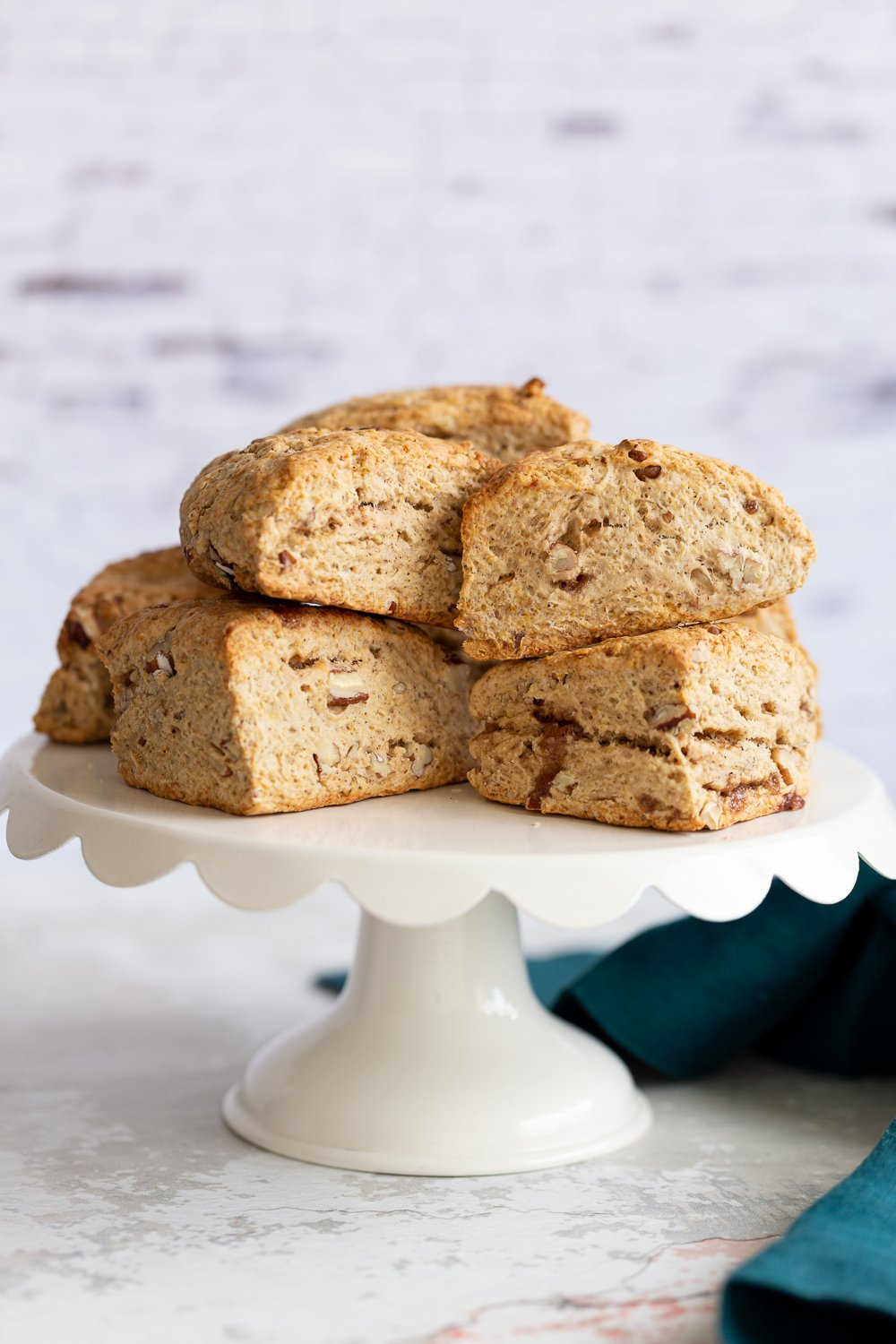 side view of vegan banana scones on a white cake stand