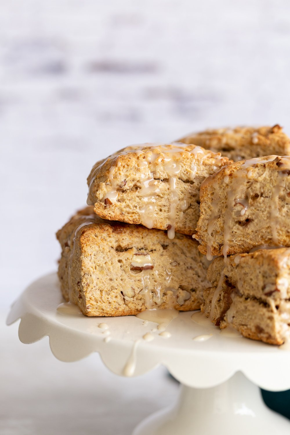 close up side view of vegan banana scones on a white cake stand