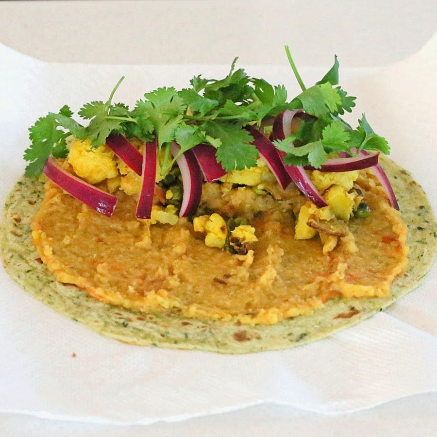 wheat tortilla topped with red lentil hummus, leftover aloo gobi, pickled onions and fresh cilantro