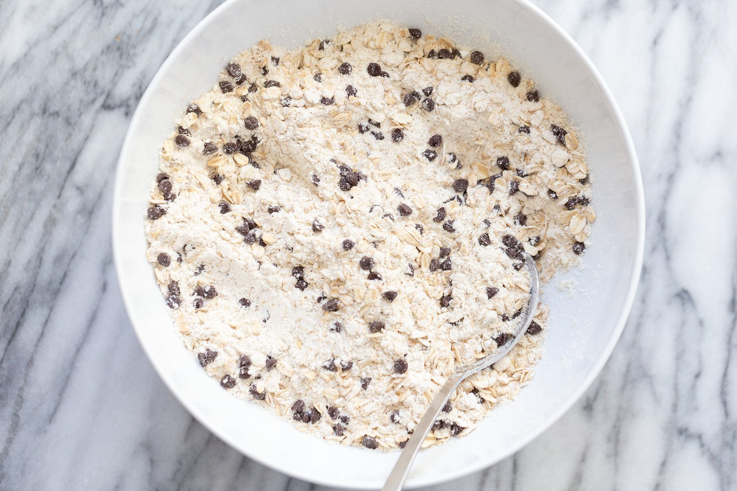 dry ingredients for vegan oatmeal chocolate chip waffles being stirred in a white bowl